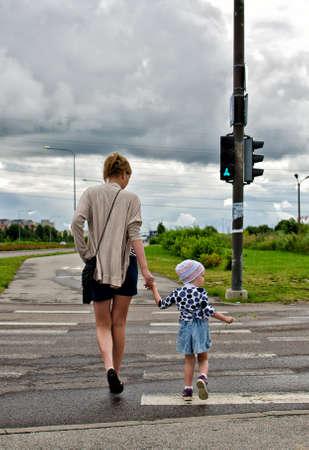 crosswalk: Mother and little daughter on zebra crossing