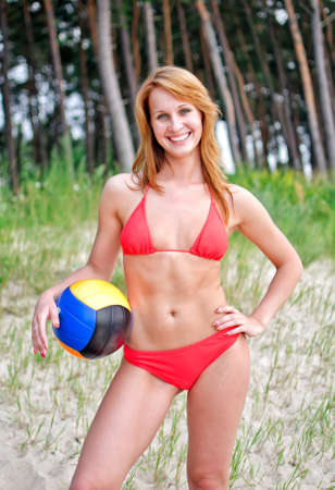 Pretty girl posing with the ball on the beach photo