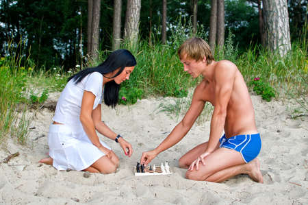 semi nude: Young couple playing chess on the beach