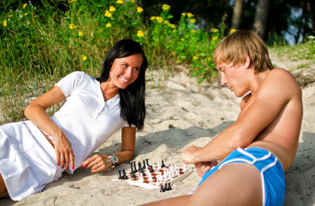 Young couple playing chess on the beach Stock Photo - 14716308