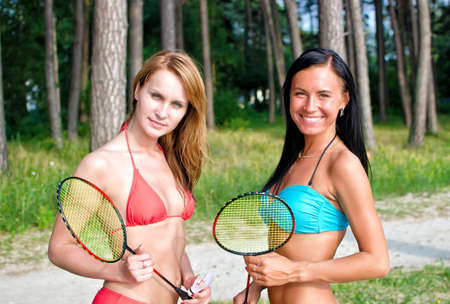 Two girls posing with badminton rackets on the beach photo