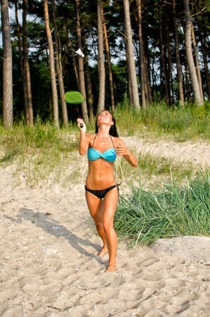 Pretty woman playing badminton on the beach photo