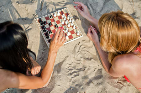Two girls playing chess on the beach photo