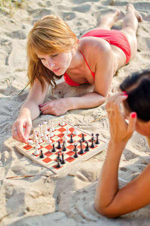 Two girls playing chess on the beach Stock Photo - 14716324