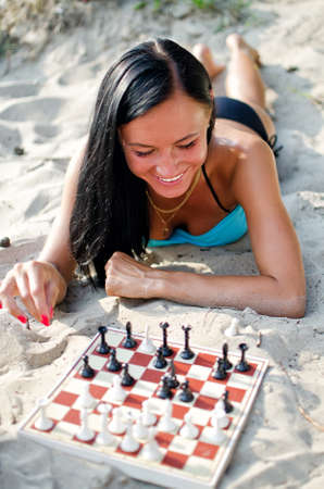 Portrait of pretty woman playing chess on the beach photo