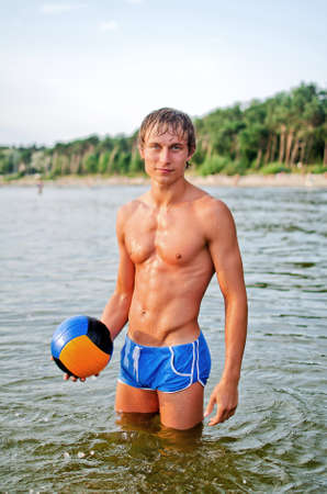 Young man posing with the ball in the sea Stock Photo - 14716298