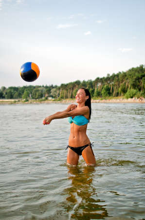 Young woman playing volleyball in the sea photo