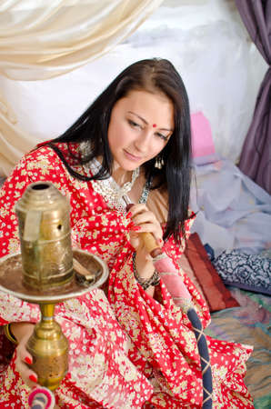 Young Indian girl in traditional red clothing with Hookah photo