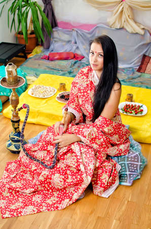 Young Indian girl in traditional red clothing with Hookah
