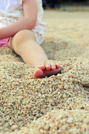 Close up toddler foot on a sandy beach photo