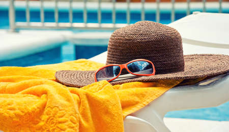 the chaise lounge: Straw hat with towel near the swimming pool