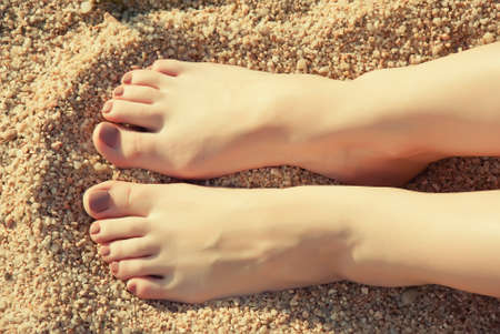 Close up female feet at sandy beach photo