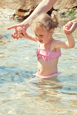Cute little girl having fun in the sea photo