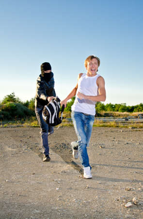 Thief in mask stealing a backpack Stock Photo - 14854958