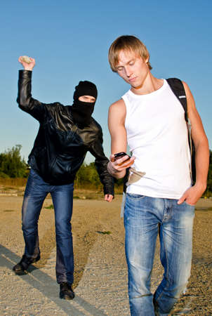 Bandit in mask trying to rob young man Stock Photo - 14854962