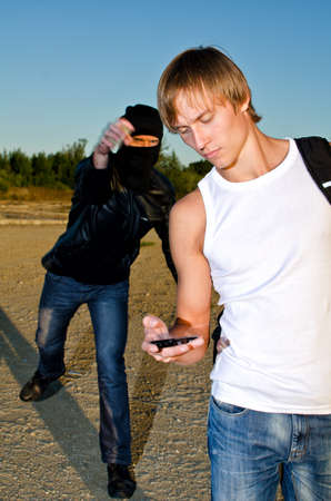 Bandit in mask trying to rob young man Stock Photo - 14854974