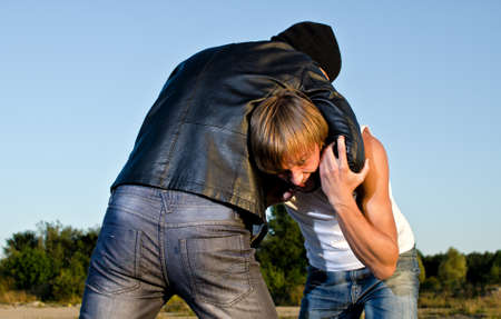 aggressive people: Two men fight outdoors. Robbery concept