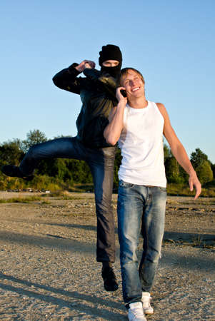 Bandit in mask trying to rob young man photo