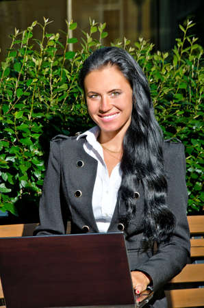 Attractive businesswoman with notebook sitting in city park photo