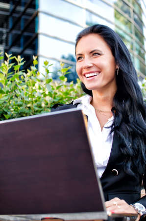 Attractive businesswoman with notebook in city park photo