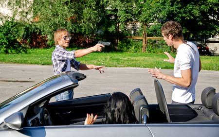 pistolas: Bandit con una pistola amenazando joven pareja en el coche Foto de archivo