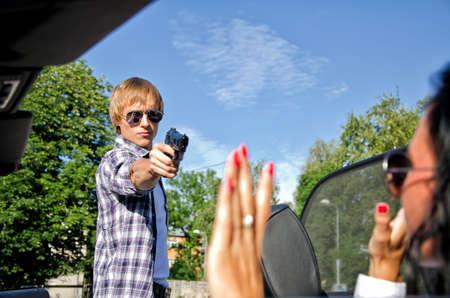 car theft: Bandit con una pistola amenazando mujer joven en el coche Foto de archivo