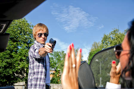 Bandit with a gun threatening young woman in the car Stock Photo - 14902781