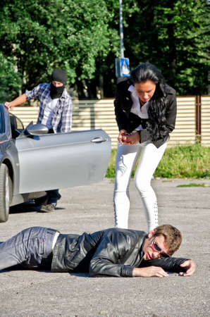 Male thief stealing a car while his accomplice distracts female driver Stock Photo