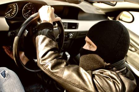 car theft: Bandido en la m�scara de robar un coche. Primer plano
