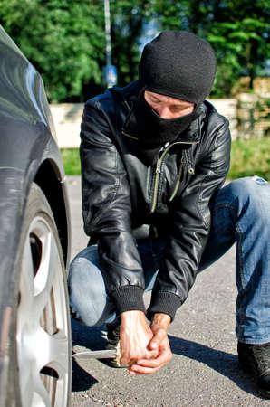 venganza: El hombre en la m�scara pincha un neum�tico de coche. Revenge concepto