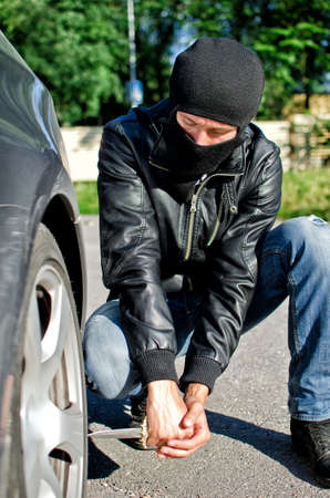 Man in mask punctures a car tyre. Revenge concept photo