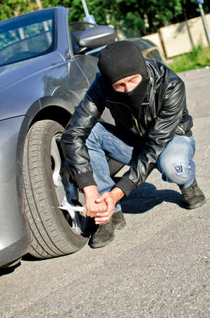 revenge: Man in mask punctures a car tyre. Revenge concept