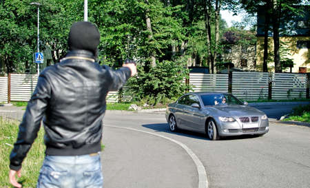 Man in mask pointing gun toward car. Robbery concept photo