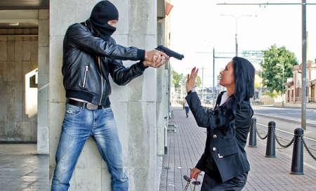 bandidas: Bandit con una pistola amenazando mujer joven en la calle Foto de archivo