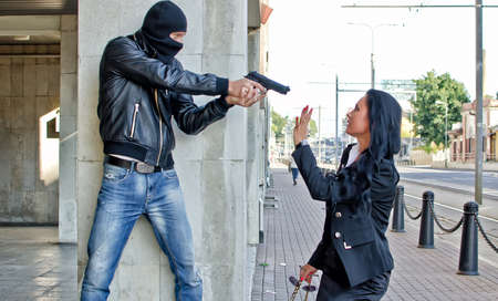 Bandit with a gun threatening young woman in the street Stock Photo - 14902640