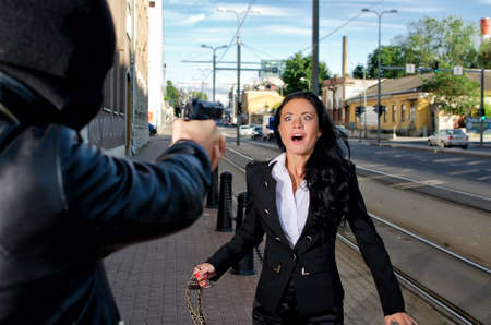 Bandit with a gun threatening young woman in the street Stock Photo - 14902681