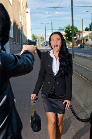 Bandit with a gun threatening young woman in the street photo
