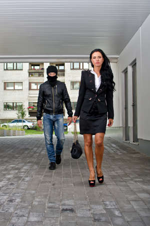 thug: Bandit in mask following businesswoman. Robbery concept Stock Photo