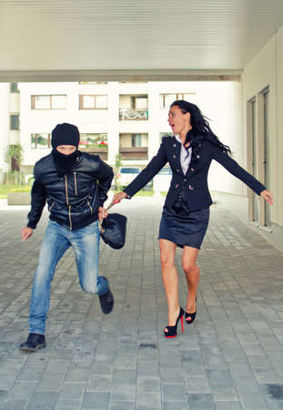 Bandit stealing businesswoman bag in the street Stock Photo - 14902698