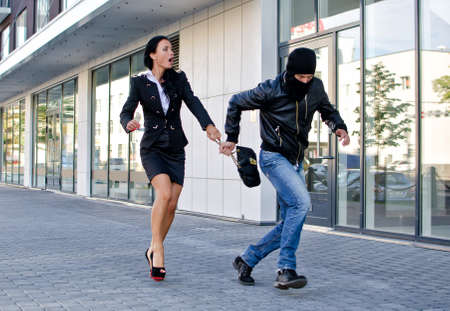 Bandit stealing businesswoman bag in the street Stock Photo - 14902682