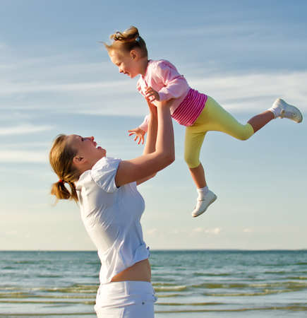 Mother and daughter having fun near the sea photo