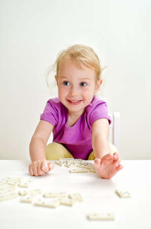Cute little girl playing domino at the table photo