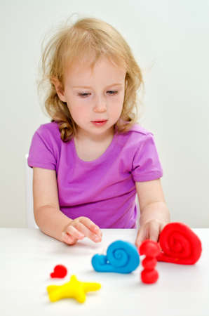 Liitle girl learning to use plasticine photo