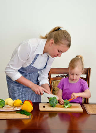 Mother and daughter preparing food. Cutting broccoli with knife. photo