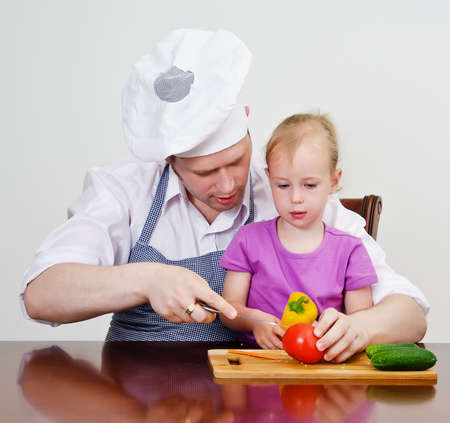 Little girl and her father cutting vegetables in the kitchen photo