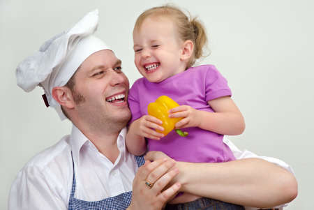 Little girl and her father having fun in the kitchen photo