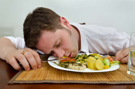 Drunk man sleeping in his dinner plate photo
