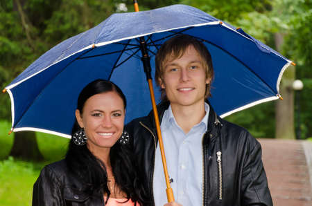 Portrait of young couple under umbrella in the park photo