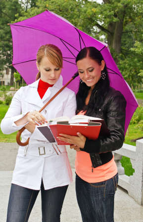 Two female students under umbrella outdoors Stock Photo - 15148409