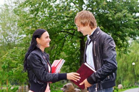 Estudiante femenino que habla con amigos al aire libre Foto de archivo